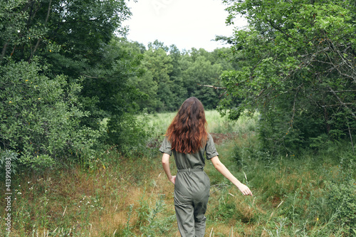 Fototapeta happy brunette woman in overalls on a meadow in the forest back view obraz