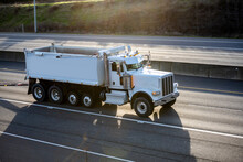 Working Horse Big Rig Tipper Truck With Two Trailers Running On The Highway Road With Sun Light