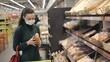 Woman wearing disposable medical mask choosing bread during shopping at bakery supermarket store. Protection and prevent measures while epidemic time.