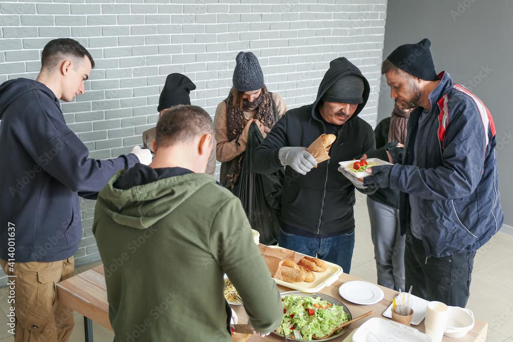 Fototapeta Volunteers giving food to homeless people in warming center