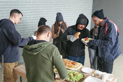 Fototapeta Volunteers giving food to homeless people in warming center obraz
