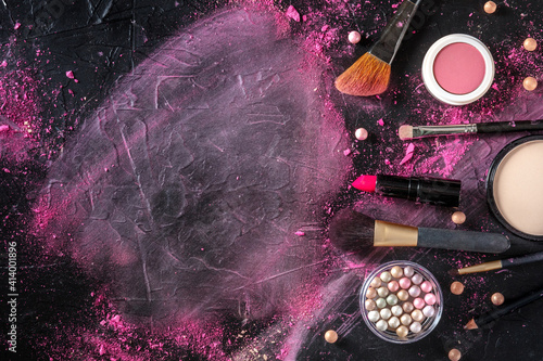 Fototapeta Makeup brushes, pearls and other products, shot from the top on a black background with a place for text obraz