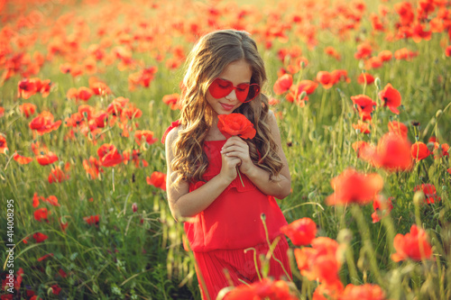 Fotografija Beautiful child girl in a field of poppies, outdoor portrait