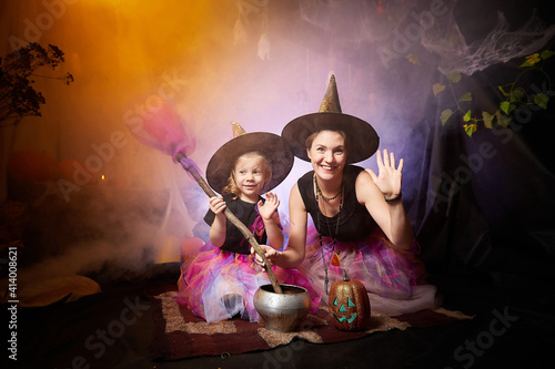 Papel de parede Beautiful brunette mother and cute little daughter looking as witches in special dresses and hats conjuring with a pot in room decorated for Halloween