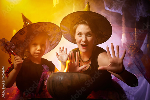 Photo Beautiful brunette mother and cute little daughter looking as witches in special dresses and hats conjuring with a pot in room decorated for Halloween