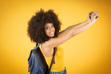 Portrait Of A Cheerful Positive Photo Of A Young Afro American Blogger, Selfie Video Blogging Calling Scream Wow Omg Color Yellow Background