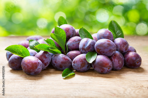 Fototapeta fresh plums with leaves on wooden table obraz