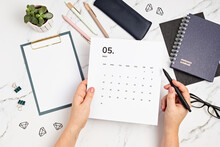 Desktop With Calendar For May And Office Supplies