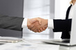 Unknown diverse business people are shaking hands finishing up meeting at the desk in office, close-up. Handshake concept
