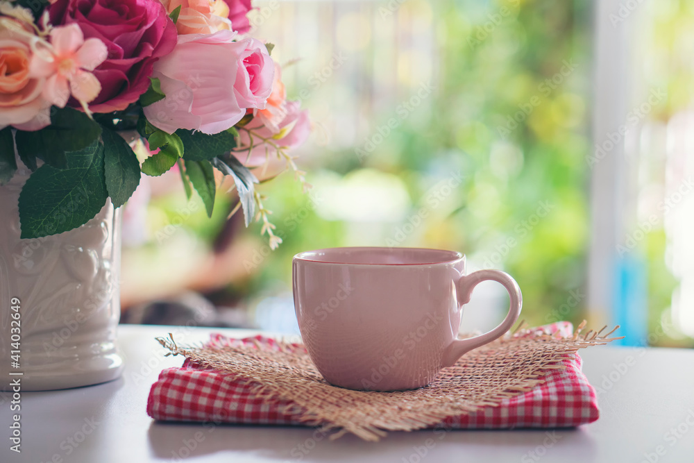 Fototapeta Coffee Break Time. A cup of coffee, and Rose Flower vase place on white home office.