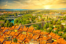 Dramatic Sunset Sky With Clouds Of Bern Old Town In Switzerland, UNESCO World Heritage Site From Cathedral Bell Tower. Aerial View Of Skyline Cityscape Of Medieval City With Arcades And Bridges.