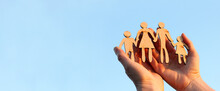 Wooden Silhouette Of A Man And A Woman With Two Children In Their Arms Against A Background Of Blue Sky. Warm Family Relationships