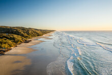 Aerial View Of Beautiful Golden Beach With Waves Crashing On The Sand On Fraser Island At Sunset, A Paradise Destination In Queensland, Australia.