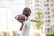 A Boy In A White Tshirt Throwing A Ball