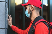 Rider Man Delivering Meal To Customers Home While Wearing Face Mask During Corona Virus Outbreak - Delivery Food Concept