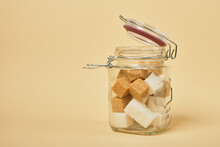 Brown And White Sugar Cubes In A Jar With A Sealed Lid, Beige Background