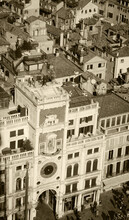 St Mark's Clocktower With Winged Lion, Bell And Madonna With Child. A View From The Campanile Tower At Piazza San Marco In Venice (Italy).  Sepia Historic Photo