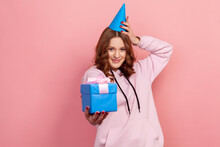 Portrait Of Cute Smiling Curly Haired Teenage Girl In Hoodie Touching Party Hat And Presenting Wrapped Blue Gift Box On Camera, Surprise. Indoor Studio Shot Isolated On Pink Background