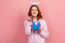 Portrait Of Positive Curly Haired Teenage Girl In Hoodie With Halo On Head Holding Wrapped Gift Box And Pointing Finger On Camera, Sincerely Smiling. Indoor Studio Shot Isolated On Pink Background