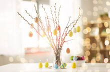 Holidays And Object Concept - Pussy Willow Branches Decorated By Easter Eggs In Vase And Candles On Table Over Bokeh Lights