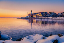 Winter In Urk With The Dike And Beach By The Lighthouse Of Urk Snow Covered During Winter, Sunset By The Lighthouse Of Urk Flevoland. Netherands