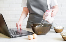 Woman In An Apron Prepares Food And Searches For A Recipe On The Internet. Online Cooking Training