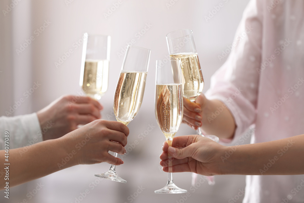 Fototapeta People clinking glasses of champagne against blurred background, closeup
