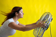 canvas print picture - A beautiful red-haired woman is cooled off standing over a large electric fan on a yellow background. Girl with hair developing in the wind. Device for cooling the air.