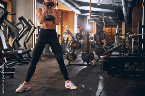 Obraz Pretty slim woman exercising with dumbbell in gym - fototapety do salonu