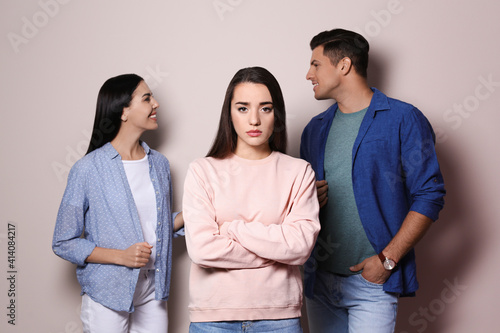 Obraz na plátně Unhappy woman feeling jealous while couple spending time together on grey backgr