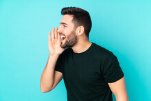 Caucasian Handsome Man Isolated On Blue Background Shouting With Mouth Wide Open To The Lateral