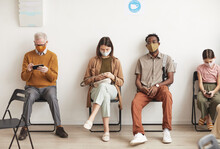 Full Length Portrait Of Multi Ethnic Group Of People Wearing Masks And Sitting In Row On Chairs While Waiting In Line At Clinic, Copy Space