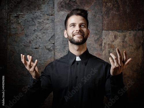 Obraz na płótnie Portrait of handsome young catholic priest preaching looking up smiling