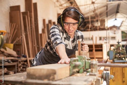 Fototapeta Frau in der Schreiner Ausbildung beim Holz hobeln obraz