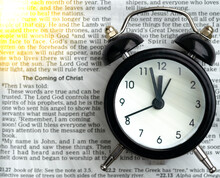 Black Alarm Clock On The Open Bible On A White Surface