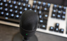 Microphone, Mic Condenser Black Metallic, Blur Keyboard Background.