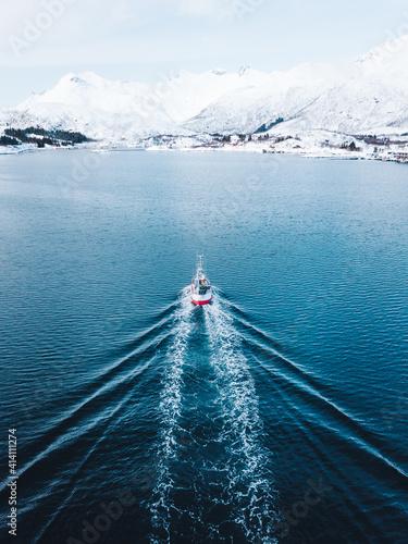 Obraz na plátně Vertical shot of a ship sailing in the sea in Lofoten, Northern Norway