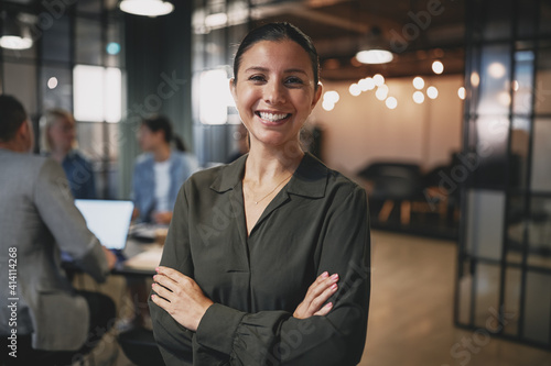 Confident young businesswoman smiling while standing in a modern office