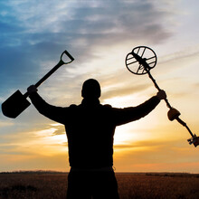 A Happy Treasure Hunter With A Metal Detector On The Background Of A Beautiful Sunset