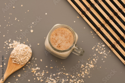 Oatmeal drink with flakes on table