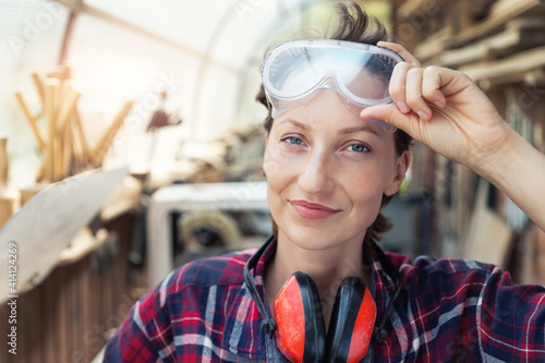 Canvas-taulu Young beautiful handy professional happy female strong carpenter portrait wearing protective goggles working in carpentry diy workshop against wood