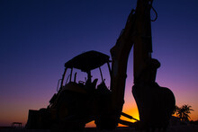 A Silhouette Shot Of A Backhoe Against The Setting Sun