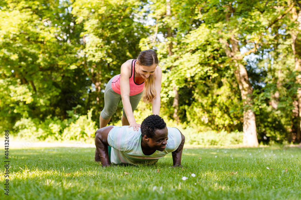 Fototapeta Mixed race couple doing fitness pushups in the park