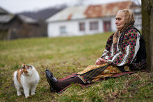 Old Woman Playing With Her Cat Outdoor