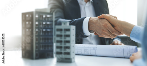Tela housing development and investment business - businessmen handshake after agreement of apartment building construction