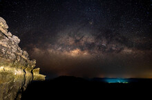 Many Stars , Milky Way And The Rocky Cliffs On The Mountain Below Are Reflected From The Village.Night Landscape Soft Focus. Space Background With Noise And Grain.