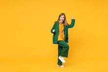 Full Length Little Blonde Excited Kid Girl 12-13 Years Old In Casual Clothes Do Winner Gesture Clench Fist Raised Up Leg Isolated On Yellow Background Children Portrait. Childhood Lifestyle Concept..