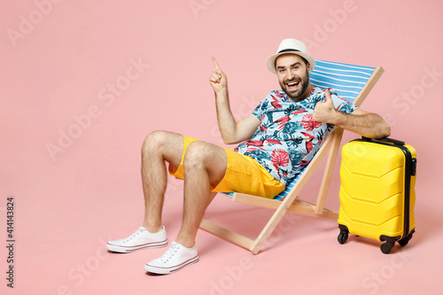 Fototapeta Full length of funny traveler tourist man in summer clothes hat sit on deck chair point finger up showing thumb up isolated on pink background. Passenger travel on weekend. Air flight journey concept. obraz na płótnie