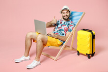 Full Length Smiling Young Traveler Tourist Man In Hat Sit On Deck Chair Work On Laptop Computer Showing Thumb Up Isolated On Pink Background. Passenger Travel On Weekend. Air Flight Journey Concept.