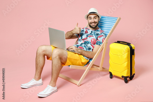 Fotografering Full length smiling young traveler tourist man in hat sit on deck chair work on laptop computer showing thumb up isolated on pink background
